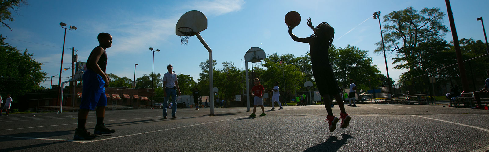 Young men playing basketball outdoors