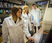 Biomedical faculty and students using equipment
