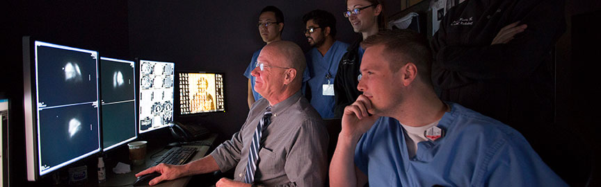 Residents and doctor in a dark room looking at scans